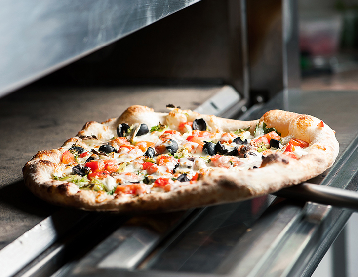 pizza lowered into commercial oven