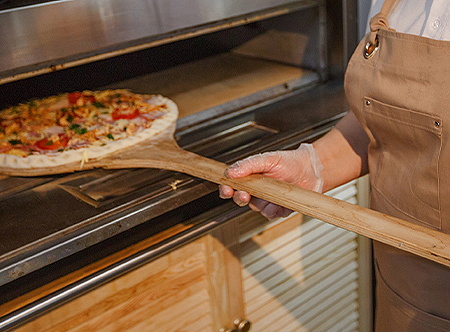 pizza being placed in home oven
